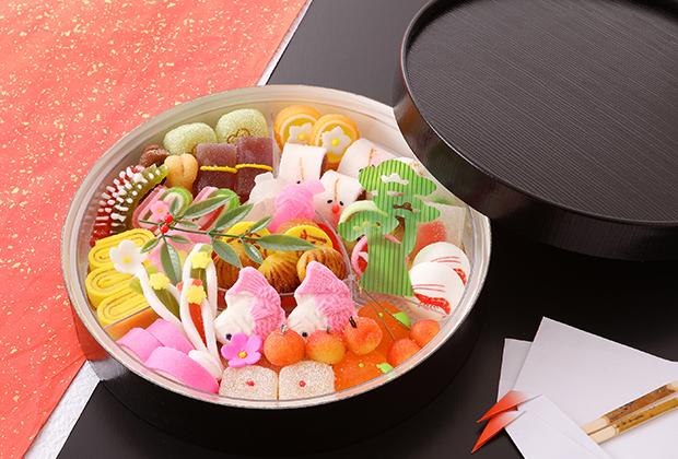 祝い肴や縁起物をかたどったひと口サイズの半生菓子が30種類詰められ、おせちのお重と見まがうほど