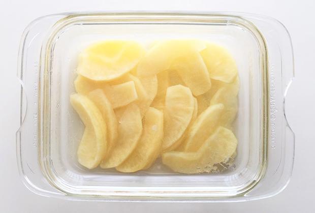 りんごは4等分にして芯を取り、皮をむいて、さらに1つを8等分に切って、くし形の薄切りにする。