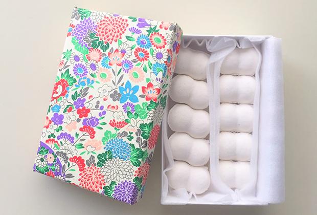 あざやかな箱を開けると真っ白な繭玉(のような)お菓子が並んでいます。