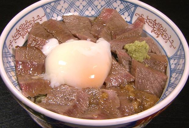 ところせましと肉が収まったどんぶりには、ワサビ、肉味噌、センターに温泉卵が添えられる。