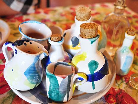 フランクさんがスペイン蒸留酒のオルホ、ハチミツやリコリスのリキュール類、ハーブティー、自家製コーヒーなど手に持って再登場