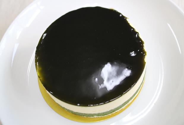 見た目はチーズケーキとは思えないキラキラ光る緑のケーキ! 天面に抹茶ジュレがのっているんです。