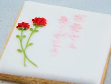 ガーベラの横に「お母さん ありがとう」と記されたメッセージ付きクッキーは、母の日用ギフトとして。