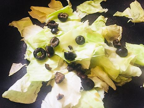 キャベツがしんなりしてきたら黒オリーブの実と液を入れ、しんなりするまで蒸し煮する