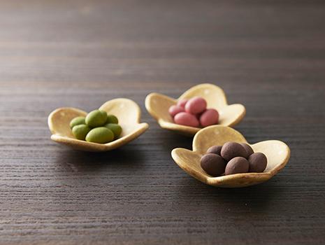 まめしょこらは、丹波産黒豆をほろ苦いチョコレートで包んだお菓子