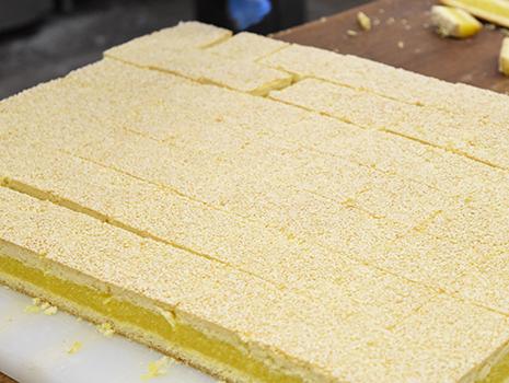 1枚の夾心餅を約60個ほどに均等に切り分け、1つずつ包装される