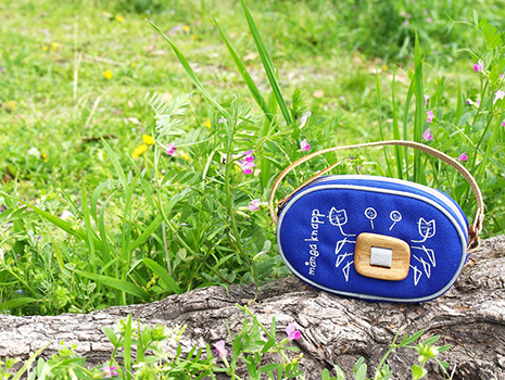「マルチケース」は、コロンとした形と刺繍、木製ボタンが一層温かみを感じさせるアイテム。